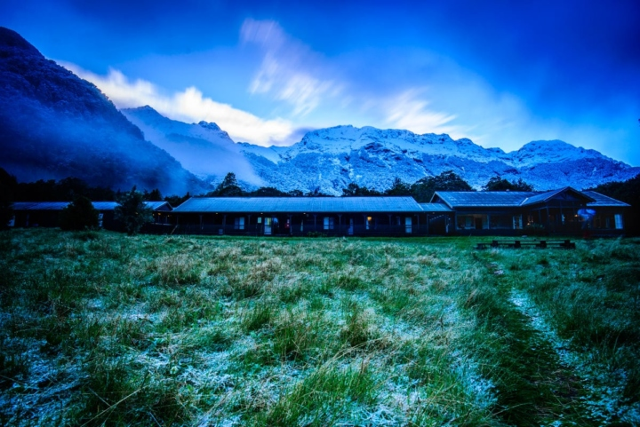 Fresh snow above a hut on Milford Track (by Ultimate hikes), with a long exposure at blue hour.