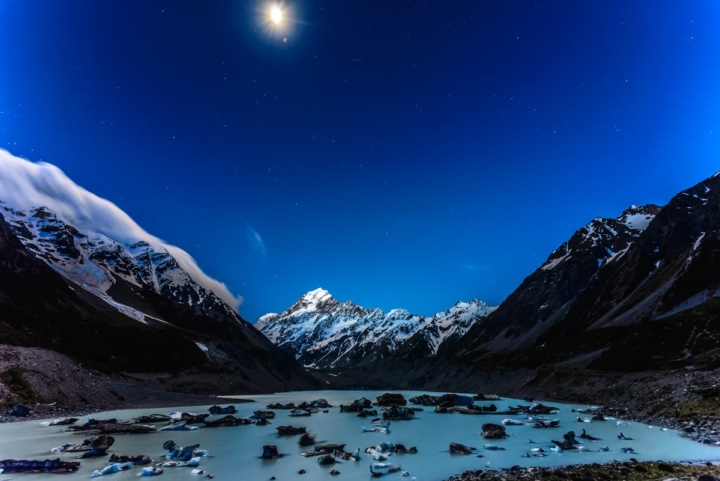 Hooker lake with full Moon over Mount Cook, New Zealand's highest summit. Icebergs on the blue lake, and stars