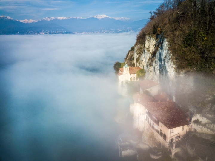 Santuario Santa Caterina Del Sasso in the fog, from a drone