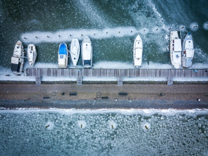 Vertical shot of boats prisoner of the ice in Marken Harbor, Netherlands
