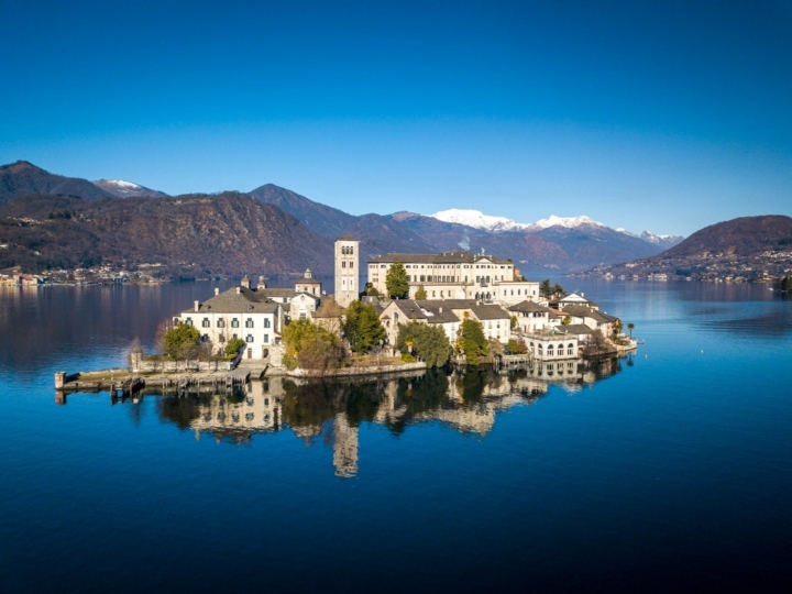 Drone view of Orta San Giulio, Novara, Italy. Nice reflexions of the sacred buildings on the calm waters of the Lago d'Orta