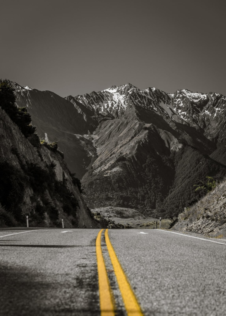 yellow line on a road, leading to a summit in new zealand