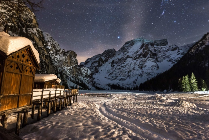 Frozen and snowy lake in the Dolomites, Italy. Path in the snow leading to the Milky Way